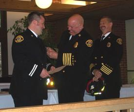 Chris Huffman receiving his Captain badge from Chief Lipe.